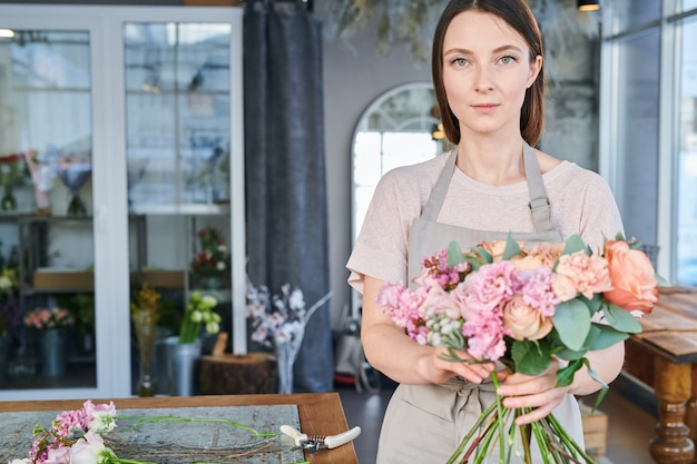 Ładna brunetka dziewczyna w odzieży roboczej stojąc przed kamerą podczas przygotowywania świeżych kwiatów na bukiety