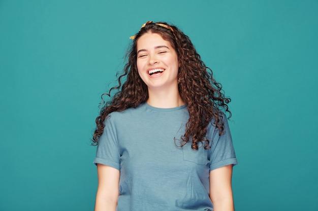 Ładna brunetka dziewczyna z kręconymi włosami, śmiejąc się głośno na niebiesko, koncepcja emocji