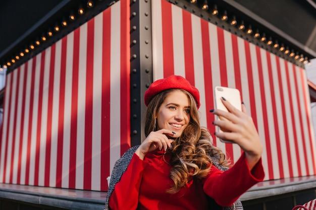 Ładna brunetka dziewczyna z wyrazem zadowolonej twarzy robi selfie na pasiastym tle