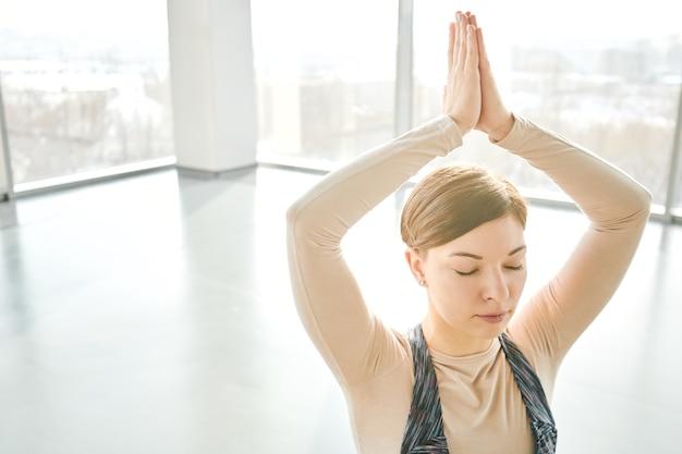 Ładna brunetka dziewczyna z zamkniętymi oczami, trzymając ręce złożone nad głową podczas relaksujących ćwiczeń jogi w siłowni