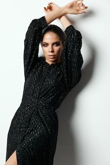 Ładna brunetka jasny makijaż czarna sukienka studio mody