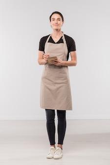 Ładna brunetka kelnerka w odzieży roboczej robi notatki w małym notatniku, stojąc przed kamerą w izolacji