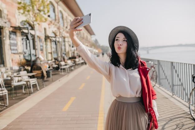 Ładna brunetka kobieta nosi elegancką bluzkę i spódnicę robiąc selfie z całowaniem wyrazem twarzy