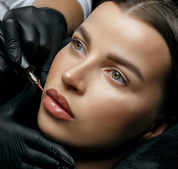 Ładna brunetka kobieta o trwałą procedurę warg w salonie piękności. strzał zbliżeniowy