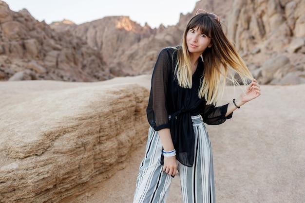 Ładna brunetka kobieta pozowanie na wydmach pustyni egipskiej.