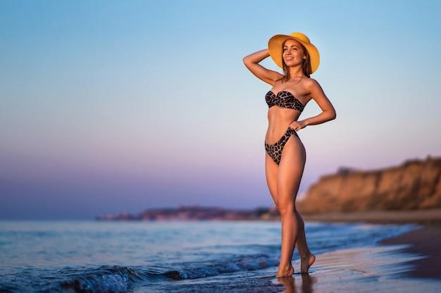 Ładna brunetka kobieta relaks na plaży nad morzem.