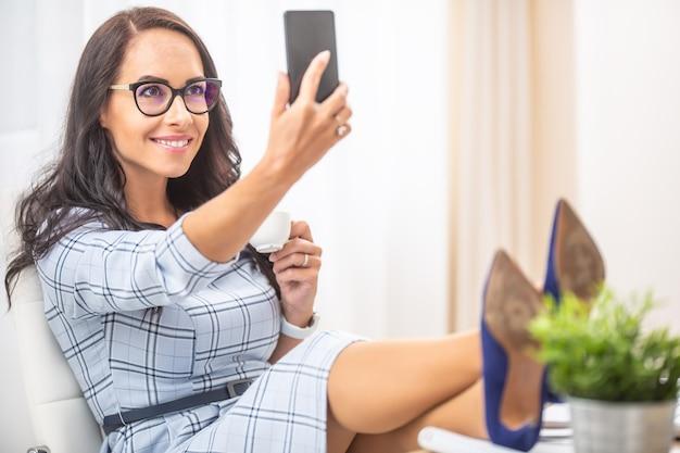 Ładna brunetka kobieta trzyma kawę, robi selfie, ma nogi na wysokich obcasach.