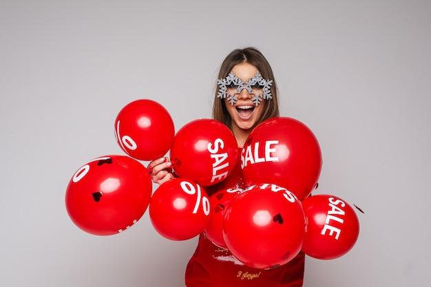 Ładna brunetka kobieta w fantazyjnych okularach z płatki śniegu, trzymając balony ze słowem sprzedaży i znakiem procentu.