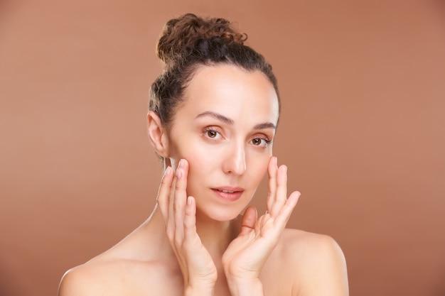 Ładna brunetka kobieta z odkrytymi ramionami, patrząc na ciebie podczas zabiegu masażu twarzy przed kamerą na ścianie z brązu