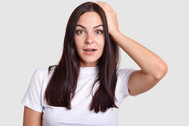 Ładna brunetka kobieta z szeroko otwartymi ustami trzymać się głowy
