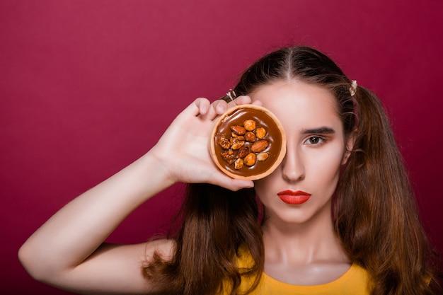 Ładna brunetka młoda kobieta z czerwonymi ustami pozowanie z ciastem karmelowym w ręku zasłaniając jej oko. pusta przestrzeń