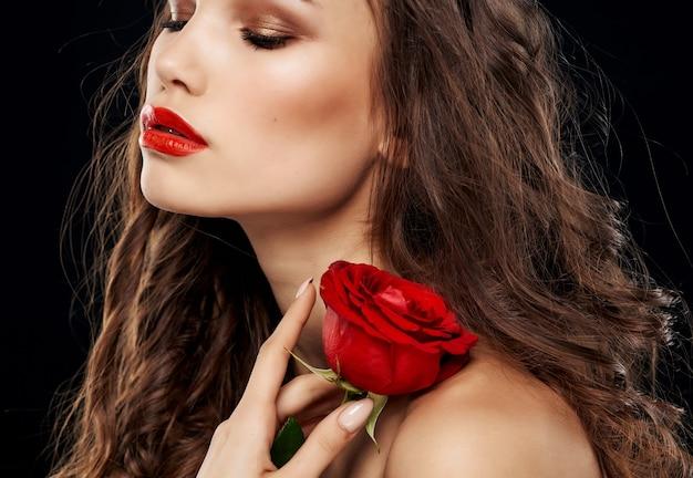 Ładna brunetka nagie ramiona czerwona róża jasny makijaż pasja