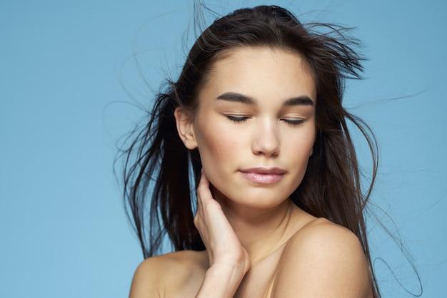 Ładna brunetka nagie ramiona długie włosy pielęgnacja skóry niebieskie tło