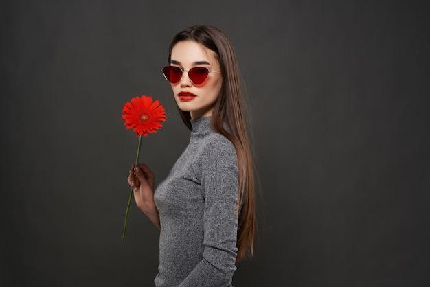Ładna brunetka nosi okulary przeciwsłoneczne czerwony glamour kwiat jasny makijaż studio