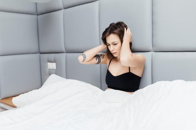 Ładna brunetka pokazuje niezdrowy wygląd rano po śnie w swoim szerokim łóżku