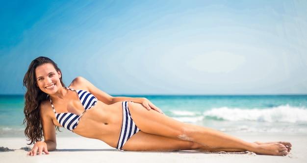 Ładna brunetka pozuje przy plażą