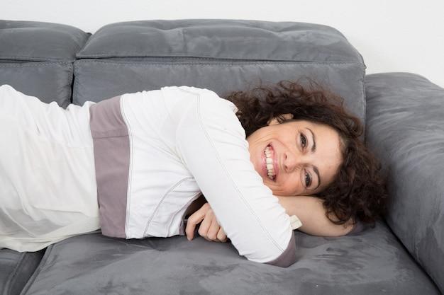 Ładna brunetka relaksuje na leżance w domu w żywym pokoju