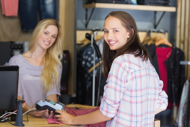 Ładna brunetka robi zakupy i ono uśmiecha się przy kamerą