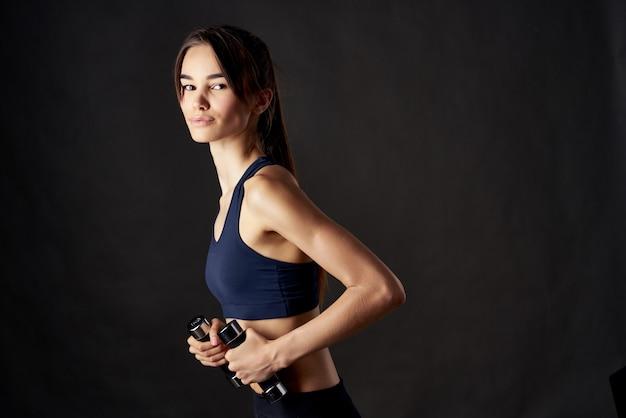 Ładna brunetka, szczupła sylwetka, ćwiczenia sportowe z hantlami w rękach na ciemnym tle