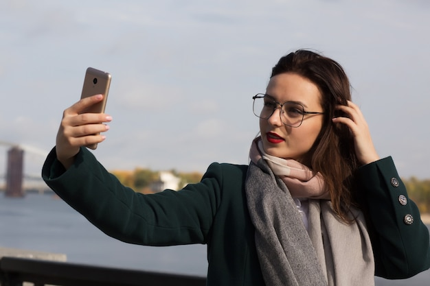 Ładna brunetka turystka robi zdjęcie selfie na wybrzeżu rzeki w kijowie