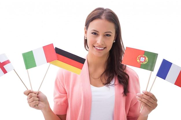Ładna brunetka uśmiecha się i trzyma flagi