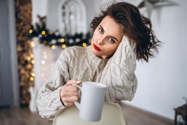 Ładna brunetka w ciepłym swetrze w domu