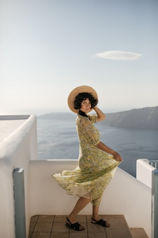 Ładna brunetka w kwiecistej sukience patrzy z przodu, trzyma wioślarza i porusza się na balkonie z widokiem na ocean