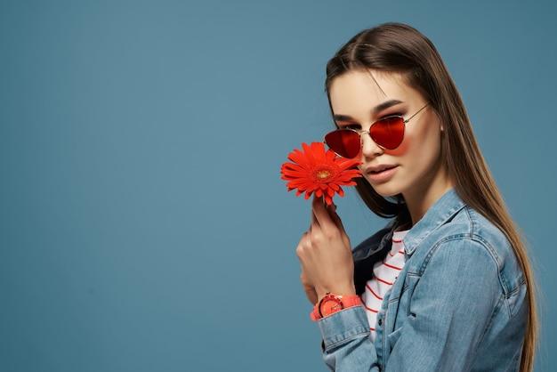 Ładna brunetka w okularach przeciwsłonecznych z czerwoną dekoracją kwiatową luksusową