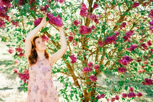 Ładna brunetka w pięknej różowej sukience pozowanie w kwitnących krzewów.