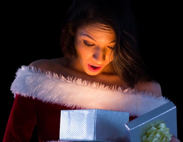 Ładna brunetka w santa prezenta otwarcia prezencie