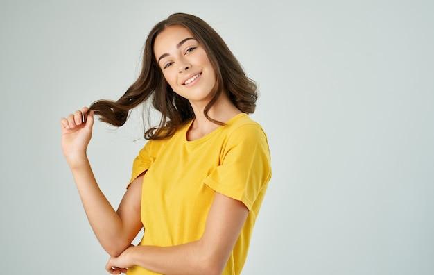 Ładna brunetka w żółtej koszulce na szarym tle uśmiech emocji.