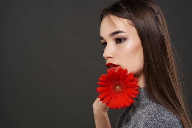 Ładna brunetka z czerwonym kwiatem luksusowa dekoracja kosmetyków