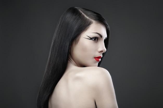 Ładna brunetka z długimi prostymi włosami na ciemnym tle