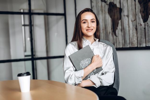 Ładna brunetka z dokumentami i filiżankami kawy, pracująca w biurze