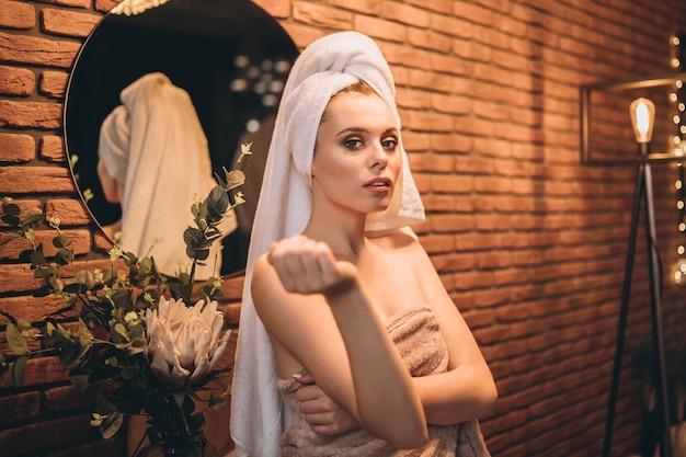 Ładna brunetka z ręcznikiem stała po prysznicu przy lustrze w łazience.