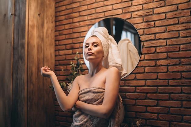 Ładna brunetka z ręcznikiem stała po prysznicu przy lustrze w łazience