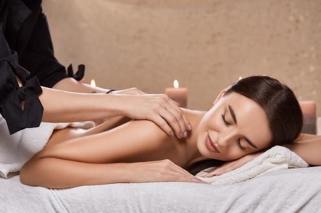 Ładna brunetka z zamkniętymi oczami podczas masażu ramienia i ramion w spa