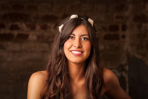 Ładna brunetki dziewczyna siedzi na rzemiennej kanapie z ściana z cegieł tłem