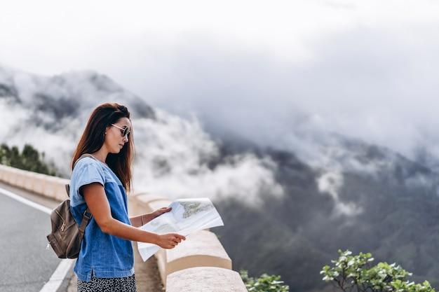 Ładna brunetki dziewczyna w okularach przeciwsłonecznych plenerowych w górach z mapą.