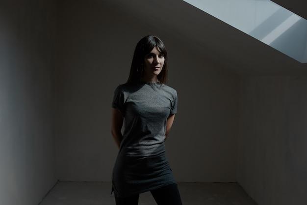 Ładna brunetki kobieta pozuje w ciemnym pokoju