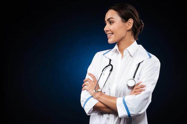 Ładna brunetki kobiety lekarka patrzeje na boku i ono uśmiecha się
