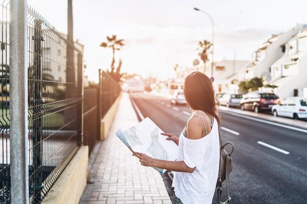 Ładna brunetki turystyczna dziewczyna z mapą w rękach na ulicznym szuka sposobie.