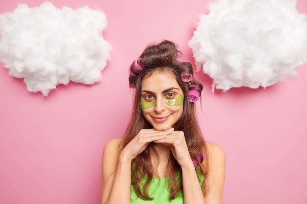 Ładna ciemnowłosa młoda kobieta z lokówkami sprawia, że fryzura nakłada kolagenowe łaty pod oczy, aby zmniejszyć obrzęki, uśmiechy przyjemnie odizolowane na różowej ścianie