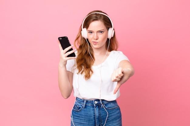 Ładna czerwona głowa kobieta czuje krzyż, pokazując kciuk w dół ze słuchawkami i smartfonem
