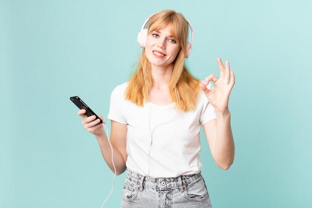 Ładna czerwona głowa kobieta czuje się szczęśliwa, pokazując aprobatę dobrym gestem i słuchając muzyki przez słuchawki