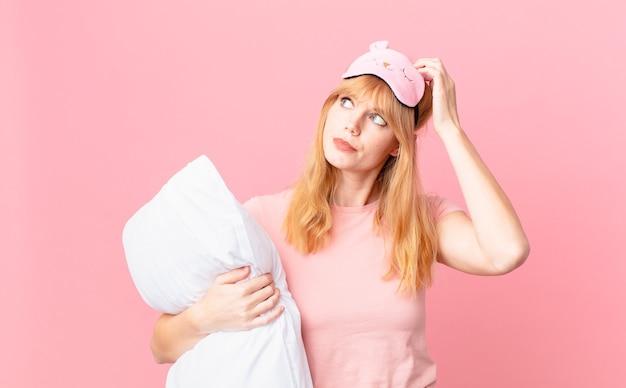 Ładna czerwona głowa kobieta czuje się zdziwiona i zdezorientowana, drapiąc się po głowie. w piżamie i trzymając poduszkę