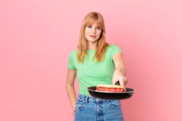 Ładna czerwona głowa kobieta gotuje hot doga z patelni