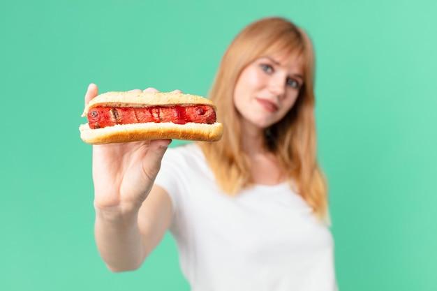 Ładna czerwona głowa kobieta trzyma hot doga.
