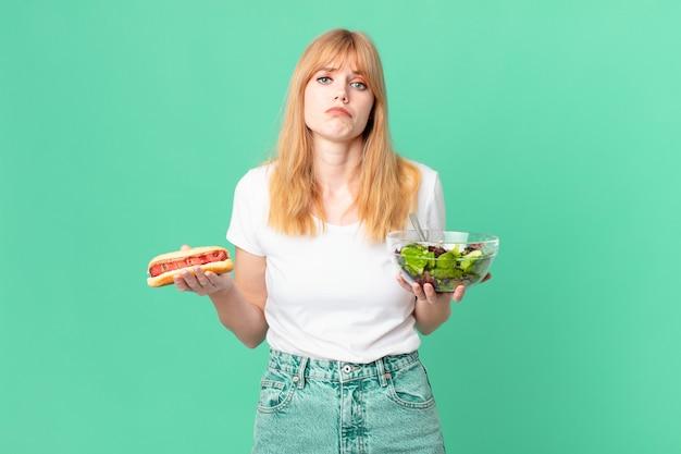 Ładna czerwona głowa kobieta trzyma sałatkę i hot doga. koncepcja diety