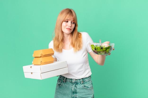 Ładna czerwona głowa kobieta trzymająca pudełka z fast foodami i sałatkę